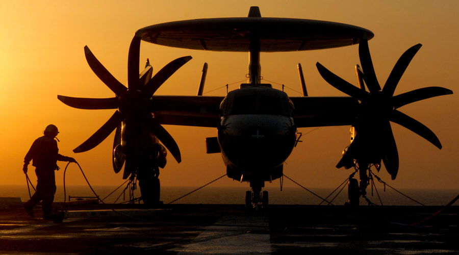 An E-2C Hawkeye is silhouetted on the flight deck of the aircraft carrier USS Harry S. Truman.